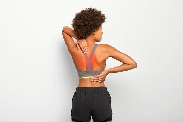 Slanke vrouw heeft chronische pijnlijke gevoelens in de rug, poseert tegen een witte achtergrond, heeft letsel of krampen, draagt een grijze top en korte broek