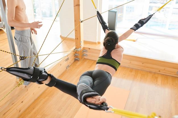 Slanke vrouw het beoefenen van yoga op trapeze