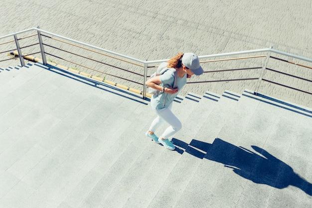 Slanke vrouw in een glb en met een rugzak die de treden in de zomer beklimt
