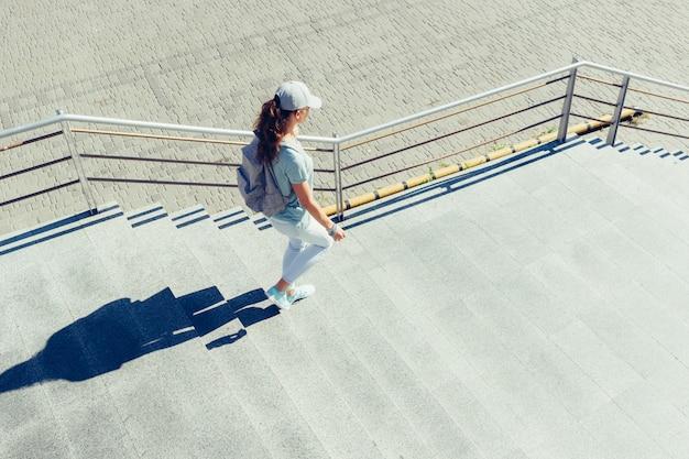 Slanke vrouw in een pet en met rugzak loopt in de zomer de trap af naar de stad