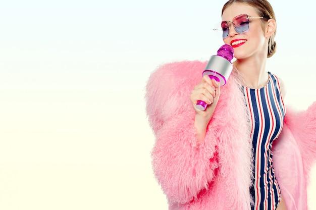 Slanke vrouw in een zwembroek met een roze pluizige bontjas en zonnebril met een roze microfoon in de hand
