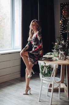 Slanke vrouw in hakken en jurk met kerstmis.