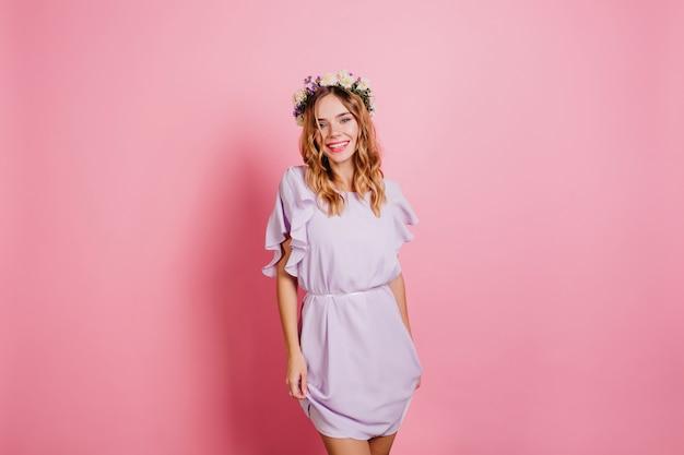 Slanke vrouw in mooie paarse jurk lachen op lichte muur
