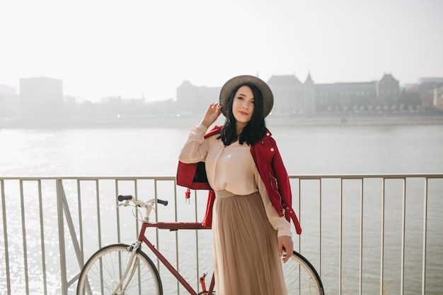 Slanke vrouw in rood jasje dat zich met fiets bij kade bevindt