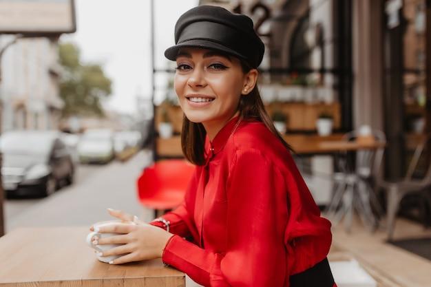 Slanke vrouw in satijnen overhemd en hoed kijkt zachtjes in de lens. bruin haar dame geniet van haar drankje