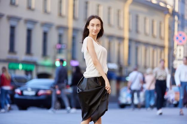 Slanke vrouw in zwarte rok loopt in de zomer buiten