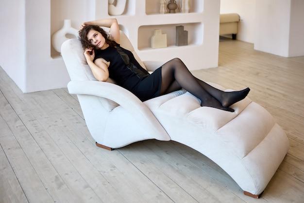 Slanke vrouw ligt op de loungestoel in de woonkamer