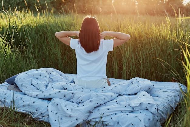 Slanke vrouw met donker haar met een wit casual t-shirt dat achterstevoren poseert met opgeheven armen, handen strekkend na het slapen, genietend van zonsopgang in groene weide in prachtige natuur.