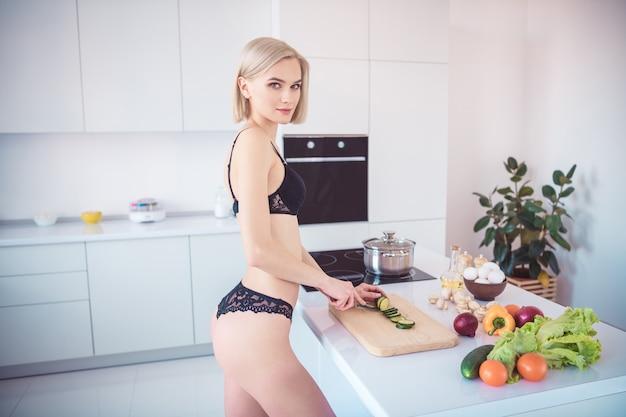 Slanke vrouw poseren in haar lingerie in de keuken