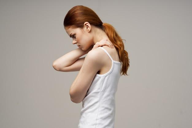 Slanke vrouw wat betreft haar handen op beige achtergrond bijgesneden weergave