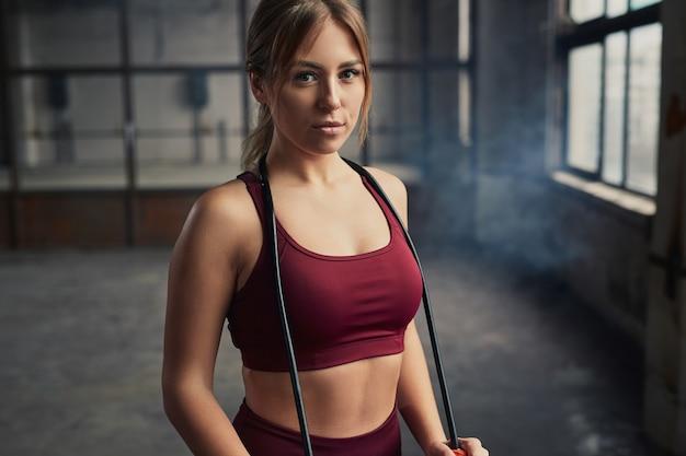 Slanke vrouwelijke atleet met touw op nek camera kijken tijdens pauze in fitnesstraining in de sportschool