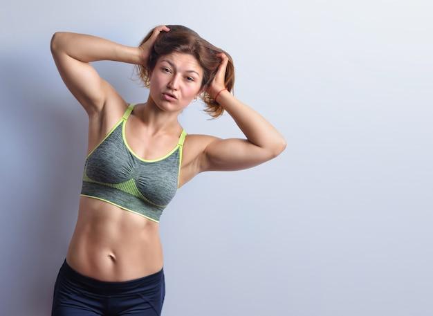 Slanke vrouwelijke fitnesscoach in grijze top en zwarte legging poseert op de achtergrond van de studio, vooraanzicht.