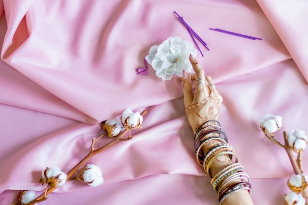 Slanke vrouwelijke hand beschilderd met indiase oosterse mehndi-ornamenten door henna. hand gekleed in armbanden en ringen houden witte bloem. lichtroze stof met plooien en katoenen takken op de achtergrond.