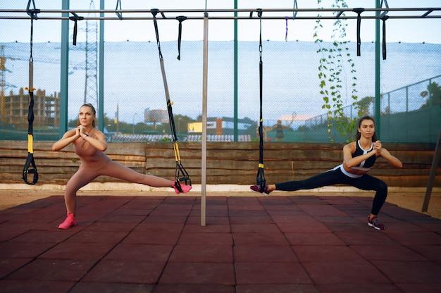 Slanke vrouwen doen evenwichtsoefening op sportveld buitenshuis, groepsfitness training