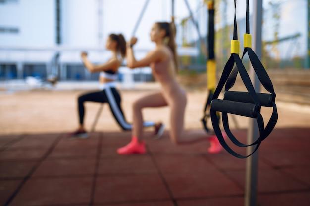 Slanke vrouwen doen stretching oefening op sportveld buitenshuis, groepsfitness training