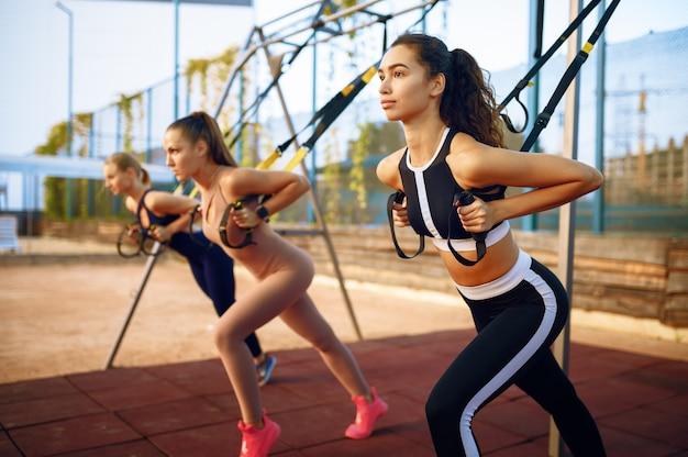 Slanke vrouwen fitte oefening met touwen op sportveld, groepstraining buitenshuis