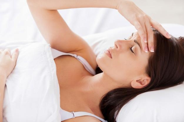 Slapeloosheid. aantrekkelijke jonge vrouw die hand in haar houdt en ogen gesloten houdt terwijl ze in bed ligt