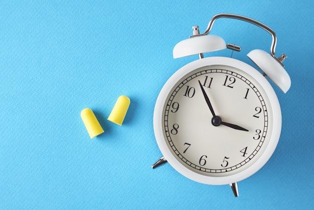 Slapeloosheid probleem concept. wekker en oordopjes op blauwe achtergrond