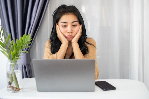 Slapeloze aziatische vrouw die zich moe en slaperig voelt met een computer op het bureau