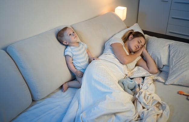 Slapeloze babyjongen die zijn moeder wakker maakt terwijl ze in bed slaapt