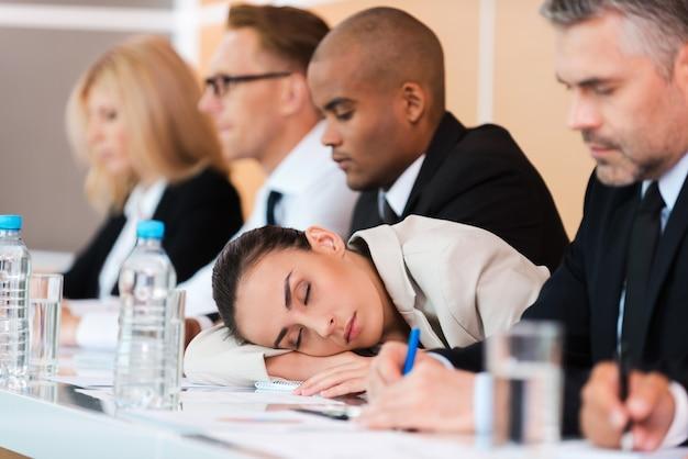 Slapen op de conferentie. moe zakenvrouw slapen terwijl ze aan tafel zit met haar collega's