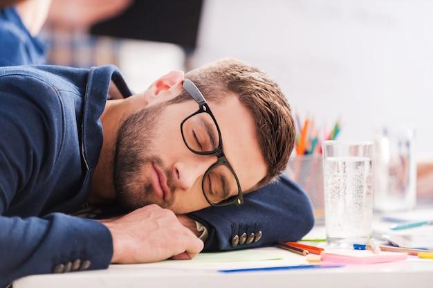 Slapen op het werk. vermoeide jonge zakenman die slaapt terwijl hij op zijn werkplek zit en met zijn hoofd naar het bureau leunt
