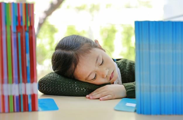 Slapend aziatisch klein kindmeisje op boekenrek bij bibliotheek