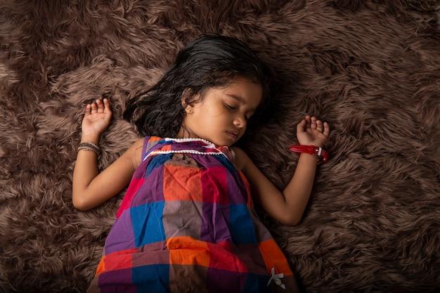 Slapend kind een meisje dat verschillende uitdrukkingen laat zien en op een synthetisch tapijt ligt