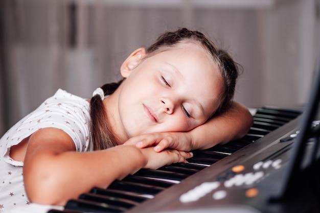 Slapend meisje met haar ogen dicht liggend met haar hoofd op de toetsen van een elektronische synthesizer