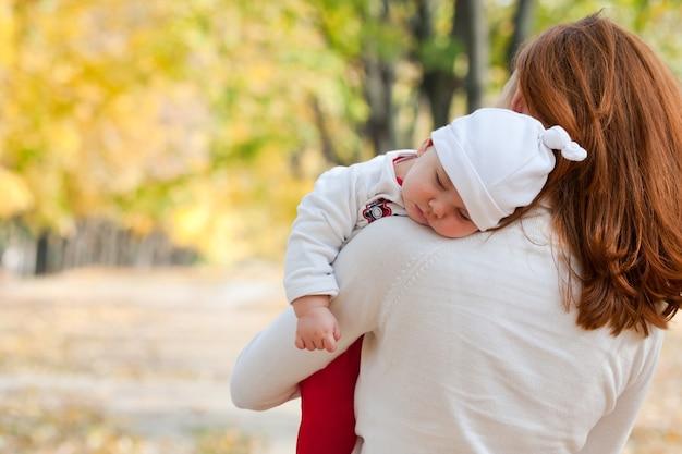 Slapend meisje op moeders schouder in herfstpark