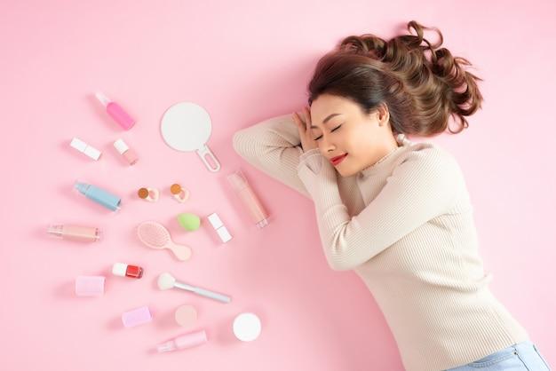 Slapende aziatische vrouw liggend op roze met haar cosmetica