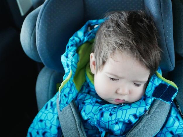 Slapende baby rijdt in een autostoeltje. gelukkig baby rijden in een auto. kinder veiligheid. leuke jongensslaap in een auto in het kinderzitje
