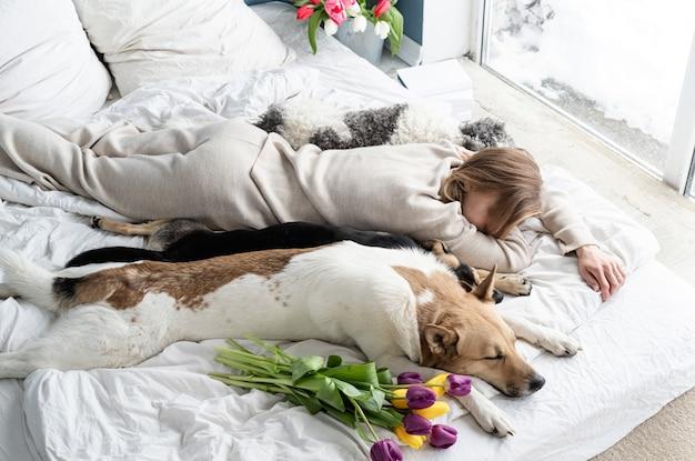 Slapende jonge vrouw die pyjama's draagt die in het bed met haar honden liggen