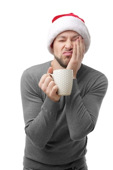 Slapende man in kerstmuts die een kopje koffie vasthoudt en de wang met de hand op de witte muur steunt
