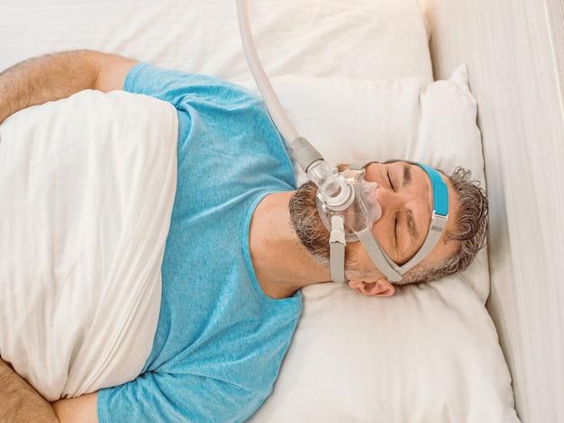 Slapende man met chronische ademhalingsproblemen met cpap-machine in bed