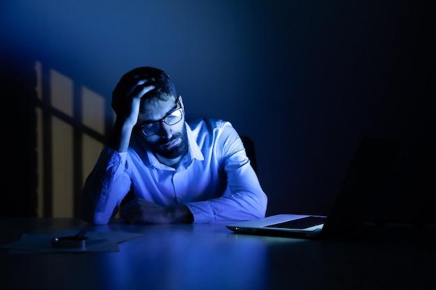 Slapende man met computer op bureau 's nachts