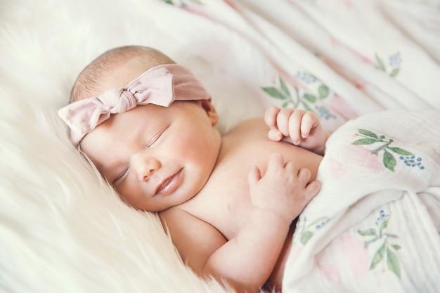 Slapende pasgeboren baby in een omslag op witte deken mooi portret van klein kind één week oud Premium Foto