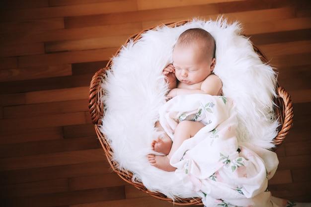 Slapende pasgeboren baby in een omslagdoek op een witte deken