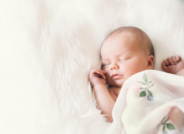 Slapende pasgeboren baby in omslag op witte deken mooi portret van klein kindmeisje één week oud