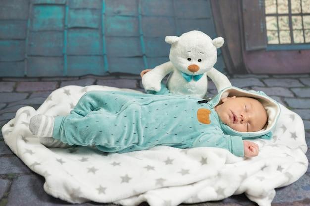 Slapende pasgeboren baby op een deken met een teddybeer