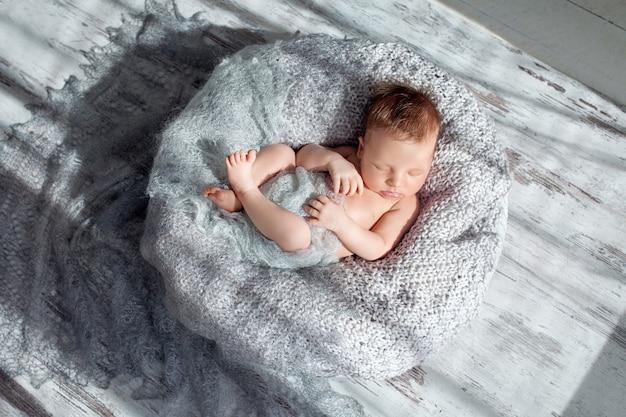 Slapende pasgeboren babyjongen ingebakerd in een nest