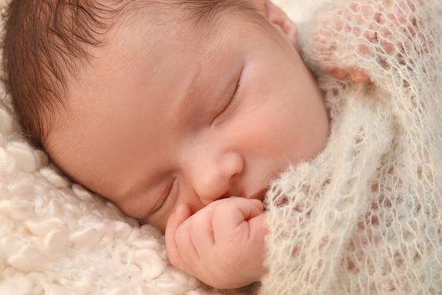 Slapende pasgeboren babyjongen op zachte plaid thuis