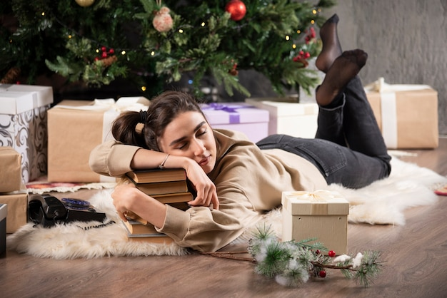 Slapende vrouw die op pluizig tapijt ligt en boeken knuffelt.