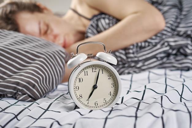 Slapende vrouw in slaapkamer en vintage wekker. wakker worden en ochtendconcept