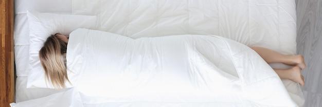 Slapende vrouw ligt op bed gewikkeld in deken eenzaamheid in het concept van de moderne samenleving