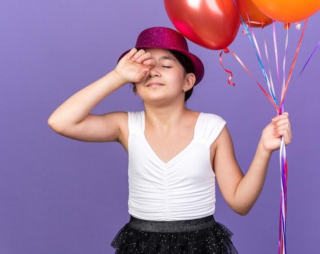 Slaperig jong kaukasisch meisje met violet feestmuts met heliumballonnen geïsoleerd op paarse muur met kopieerruimte