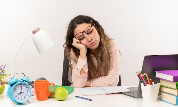 Slaperig jong mooi schoolmeisje die glazen dragen die aan bureau met schoolhulpmiddelen zitten die haar huiswerk doen hand op wang zetten met gesloten ogen die op witte muur wordt geïsoleerd