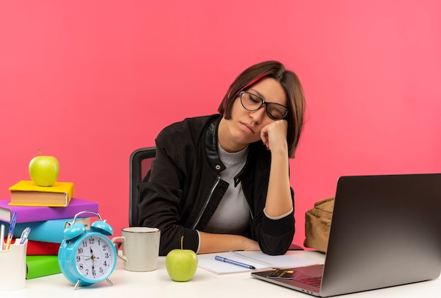 Slaperig jong studentenmeisje die glazen dragen die aan bureau zitten die hand op wang met gesloten ogen zetten die op roze muur wordt geïsoleerd