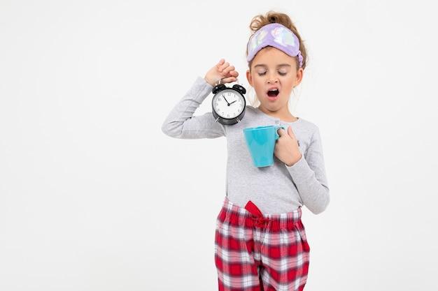 Slaperig meisje in pyjama werd net wakker en geeuwt met kopie ruimte
