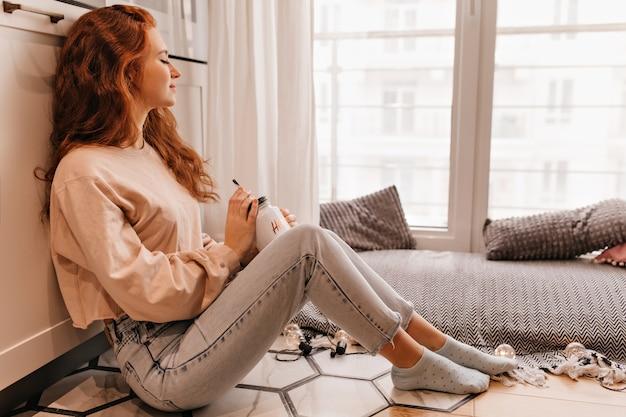 Slaperig meisje in spijkerbroek glühwein drinken in koude dag. binnenfoto van het krullende jonge vrouw stellen met kop thee.